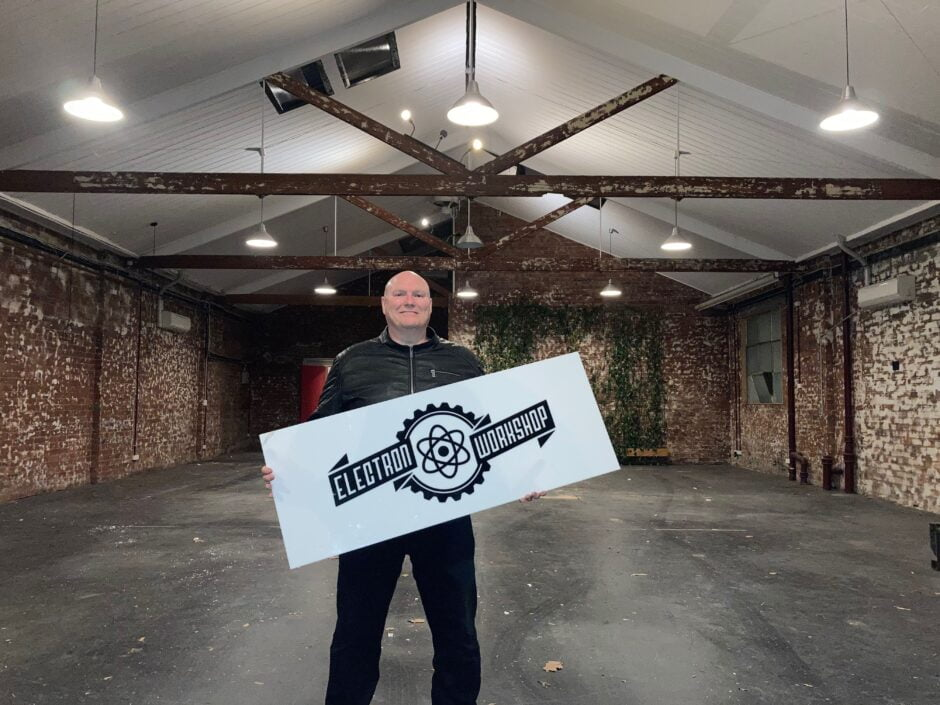 Marty standing in an empty Electron Workshop with the Electron Workshop sign from our lightbox that was mounted in the green wall.